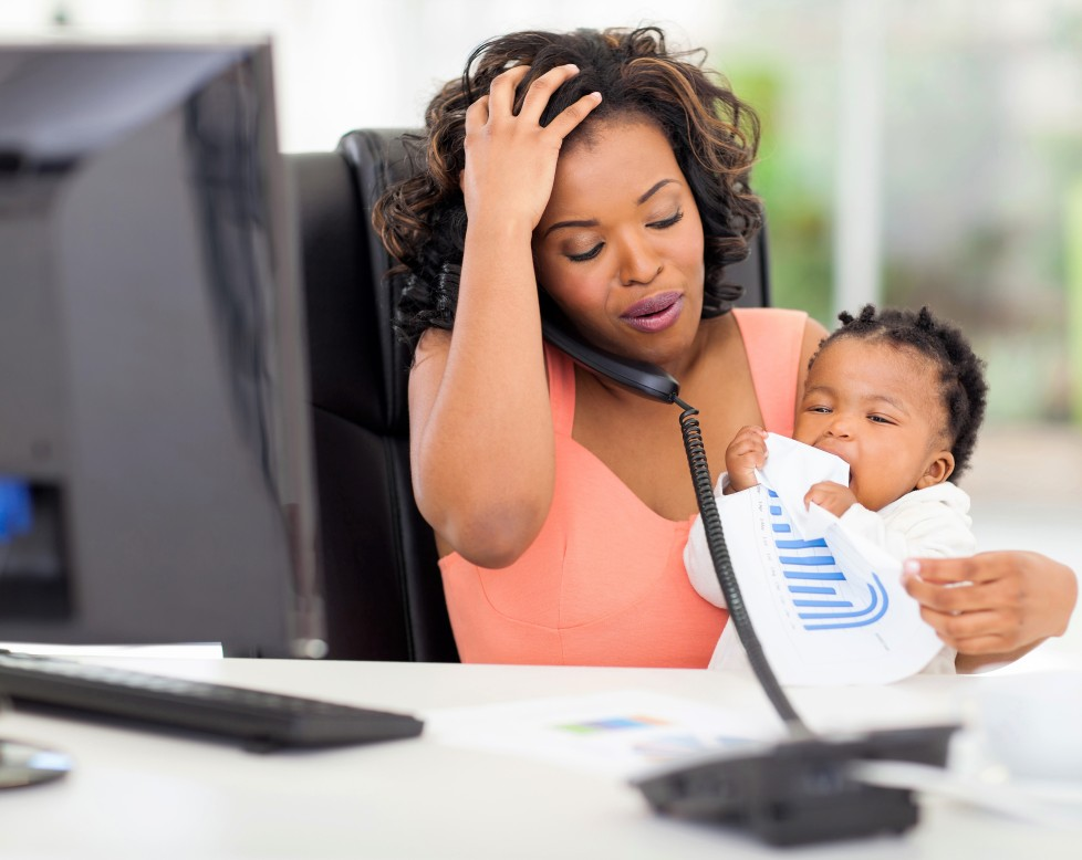 stressed african american businesswoman with baby girl in office